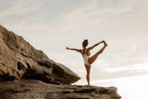 woman yoga pose on rocks near ocean