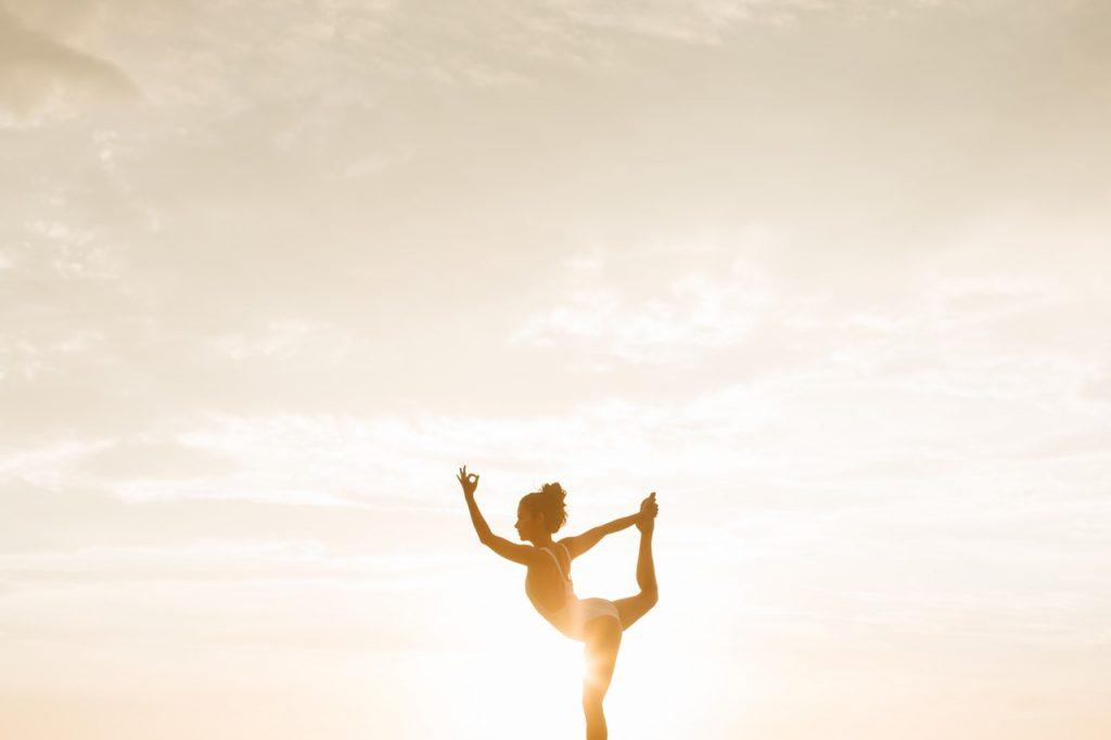 woman yoga pose sun behind